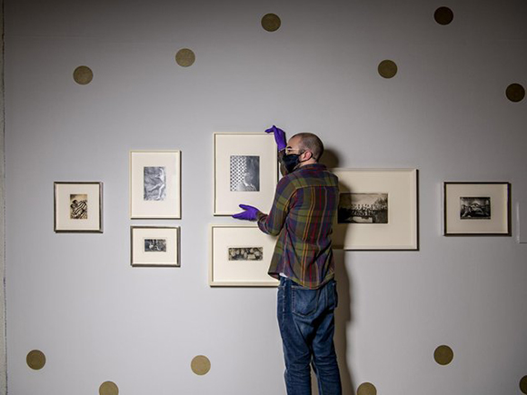 Millenium Gallery curator Ashley Gallant hanging pictures as part of new Cecil Beaton's Bright Young Things exhibition